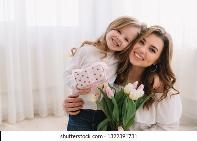 Happy mother's day. Child daughter congratulates moms and gives her flowers tulips and gift.