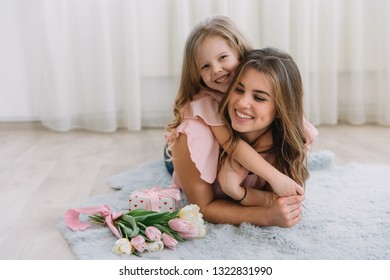 Happy mother's day. Child daughter congratulates mom and gives her flowers tulips and gift. Mum and girl smiling and hugging. Family holiday and togetherness.