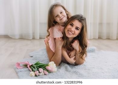 Happy mother's day. Child daughter congratulates mom and gives her flowers tulips. Mum and girl smiling and hugging. Family holiday and togetherness.