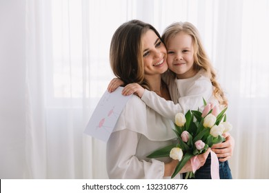 Happy mother's day. Child daughter congratulates moms and gives her a postcard and flowers tulips.