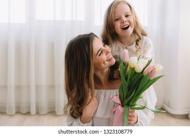 Happy mother's day. Child daughter congratulates moms and gives her flowers tulips. - Shutterstock ID 1323108779