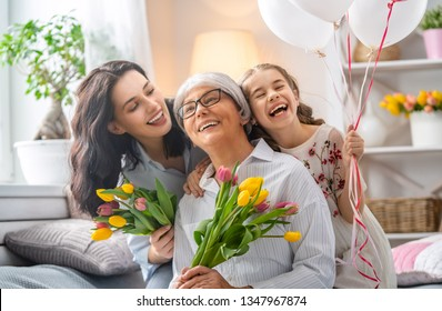 Happy mother's day! Child daughter is congratulating mom and granny giving them flowers tulips. Grandma, mum and girl smiling and hugging. Family holiday and togetherness.
