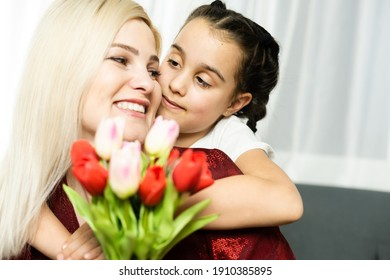 Happy mother's day. Child daughter congratulates moms and gives her a postcard and flowers tulips - Shutterstock ID 1910385895