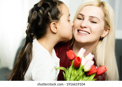 Happy mother's day. Child daughter congratulates moms and gives her a postcard and flowers tulips