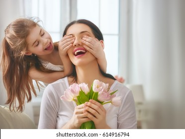Happy mother's day! Child daughter congratulates mom and gives her flowers tulips. Mum and girl smiling and hugging. Family holiday and togetherness. - Shutterstock ID 614916794