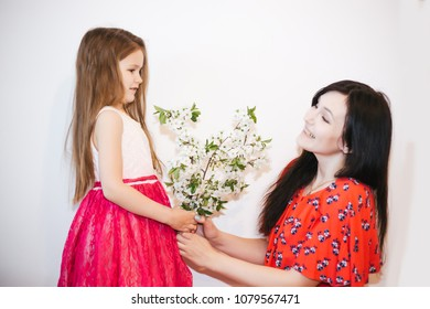 Happy mother's day! Child Girl daughter congratulates mom and gives her flowers . Mum and girl smiling and hugging. Family holiday and togetherness.