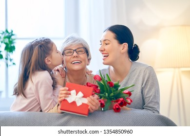Happy mother's day! Child and mom congratulating  granny giving her flowers tulips ang gift box. Grandma, mum and girl smiling and hugging. Family holiday and togetherness.