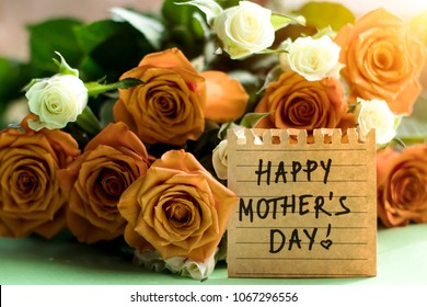 Happy Mother's Day concept. Inscription 'Happy Mother's Day' on a piece of paper with a bouquet of orange and white roses
