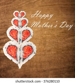 Happy Mother's day concept with sushi forming heart shapes against wooden background
