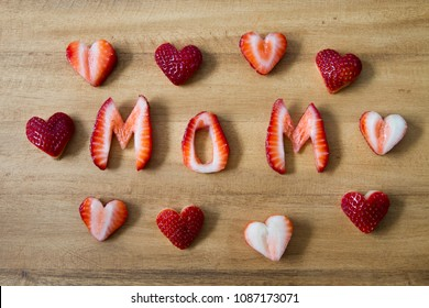 Happy Mother's Day Conceptual Image with Strawberries and heart shapes on rustic wooden cutting board.