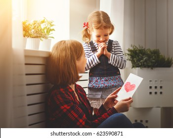 Happy mother's day! Daughter gives her mother an postcard and hugs
