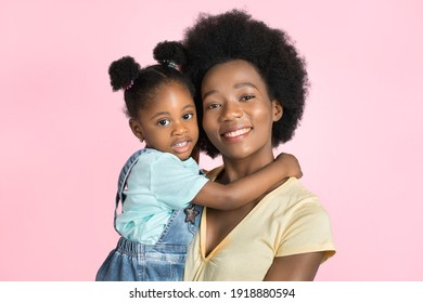 Happy mother's day, family, motherhood concept. Close up studio shot of happy pretty young African woman mom, holding her cute little daughter, posing to camera on pink background