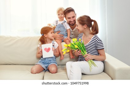 happy mother's day! father and children congratulate mother on holiday and give flowers