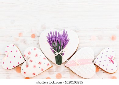 happy mother's day greeting card. cookie hearts with lavender flowers on white rustic wooden background with confetti flat lay. space for text. happy valentine's day or women's