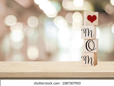 Happy mother's day greeting card, Love mom word on wooden cubes over blur background with copy space for text