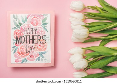 happy mothers day greeting card and white tulips on pink background