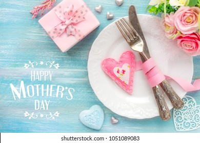Happy mother's day greeting. Table place setting with a white plate, vintage silverware tied with a pink ribbon and many different heart shape decorations, a gift and flowers