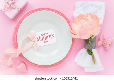 Happy Mother's Day greeting with white and pastel pink plates white linen napkin decorated with fresh peony flower, wrapped gift and an empty tag with a ribbon. Overhead view