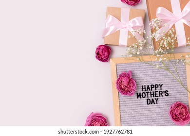 Happy Mothers day. Letter board, gypsophila and rose flowers, gifts tied with ribbons on a gray background. Festive concept with copyspace.