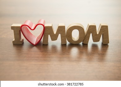 Happy Mothers day. I Love my mom Concept. Red heart and Wooden letters spelling. Image with shadows on table.