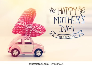 Happy Mothers Day message with a miniature pink car carrying a heart cushion