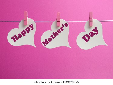 Happy Mother's Day message written across white heart shape gift tags hanging from pegs on a line against a pink background.