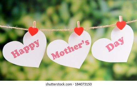 Happy Mothers Day message written on paper hearts with flowers on bright background