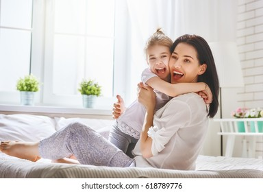 Happy mother's day! Mom and her daughter child girl are playing, smiling and hugging. Family holiday and togetherness.