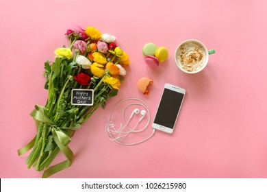 Happy Mother's Day note on the buttercup flowers, cup of cappuccino, macaroons cake and mobile with headphones on the pink background, Happy Mother's Day concept.