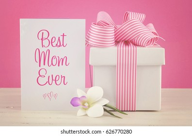 Happy Mothers Day pink and white gift with Best Mom Ever greeting card, on white shabby chic distressed wood table, with applied retro style filters.
