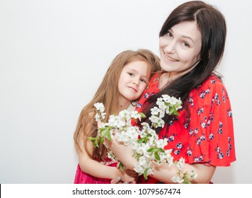 Happy mother's day! Pretty Child daughter congratulates mom and gives her flowers . Mum and girl smiling and hugging. Family holiday and togetherness.
