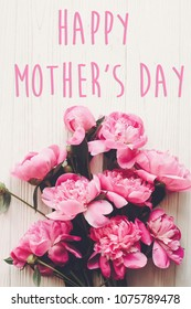 happy mother's day text on pink peonies bouquet on rustic white wooden background, top view. floral greeting card concept, flat lay. mothers day. vertical spring image