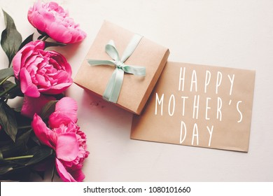 happy mother's day text on craft card and pink peonies bouquet with gift box on rustic white wooden background in light. floral greeting card concept, flat lay. mothers day