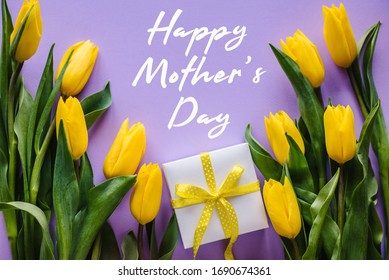 Happy mother's day. Text sign with yellow tulips and gift box on violet background. Floral greeting card concept. Holiday greeting card for Mother's Day! Top view, flat lay.