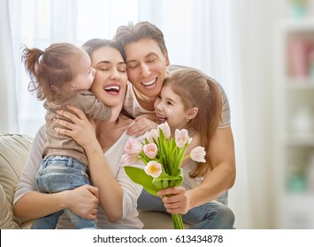 Happy mother's day! Two children daughters with dad congratulate mom and give her flowers tulips. Mum and girls smiling and hugging. Family holiday and togetherness.