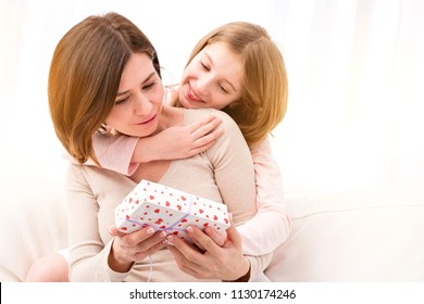 Happy Mother's Day, happy woman's day, happy birthday. Beautiful little girl giving her mother small wrapped gift box. Daughter embracing and congratulating her mum