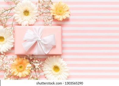 Happy Mother's Day, Women's Day, Valentine's Day or Birthday Pastel Pink Background. Floral flat lay greeting card with beautifuly wrapped present and gerbera flowers.
