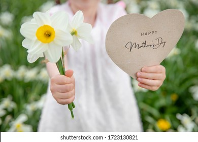 Happy Mother's Day written on a paper card with flowers held by a girl on a flower and grass background
