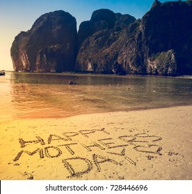 Happy Mother's Day written on the sand on a flat yellow beach. Mountains and clear ocean in the background. Phi-Phi Island, Thailand. Holiday, travel, sport, recreation. Retro vintage toning effect