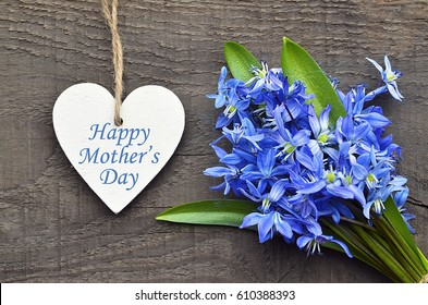 Happy Mother's Day.Blue Scilla flowers and decorative wooden heart on old wooden background.Mother's Day greeting card