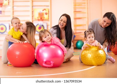 Happy mothers and nursery babies on fitness ball in gym. Gymnastics for kids on fit-ball.