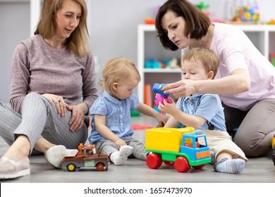 Glückliche Mütter mit ihren Babys spielen in der Kinderbetreuung