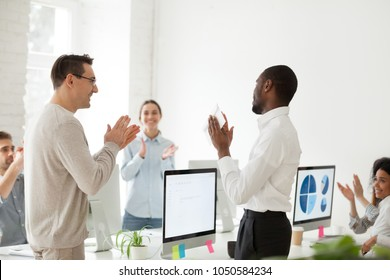 Happy motivated african american employee receiving envelope with reward or bonus from caucasian boss appreciating good work results while business team applauding supporting colleague in office
