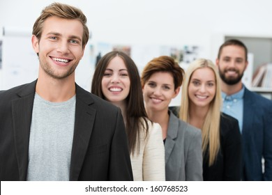 Happy motivated business team of diverse young professional men and women standing in a receding row headed by their handsome young team leader
