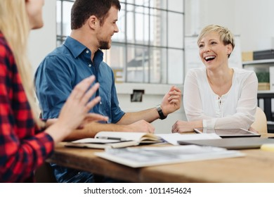 Happy motivated business team enjoying a laugh with low angle focus to a pretty young blond woman