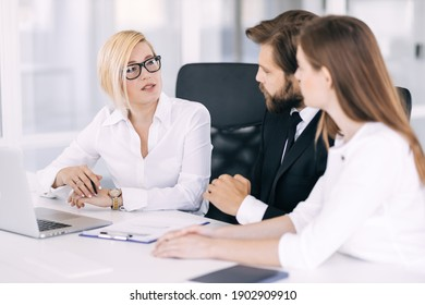 Happy motivated diverse business people work together, collaborate in an office meeting, colleagues discuss financial project ideas in a boardroom briefing.