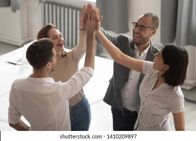 Happy motivated diverse business work team people employees group giving high five together engaged in teambuilding celebrate success good teamwork result shared win promise trust integrity concept