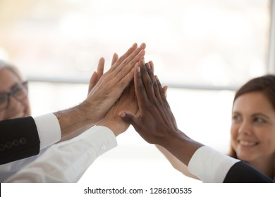 Happy motivated multiracial businesswoman and businessman giving high five stack their hands together celebrating victory sharing success and great deal. Goal achievement unity and teamwork concept