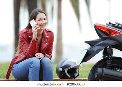 Happy motorbiker calling insurance on phone after breakdown and looking at camera sitting beside her motorbike