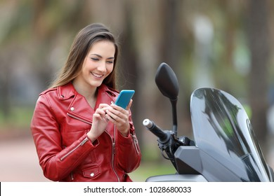 Happy motorbiker using a smart phone sitting on a motorbike